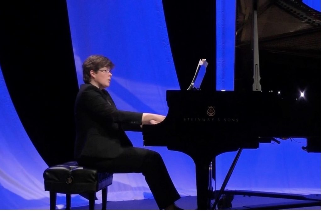 woman playing a grand piano